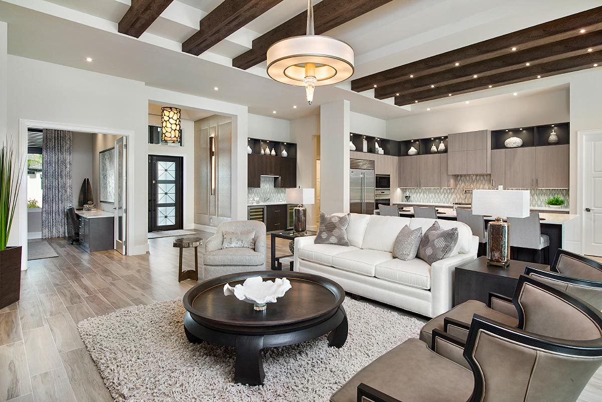 The living room has a beamed ceiling and a wide plank flooring topped by a beige area rug.