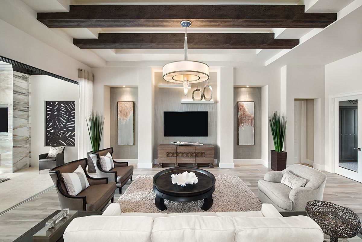Cozy seats, a round coffee table, glass chandelier, and a wall-mounted TV complete the living room.