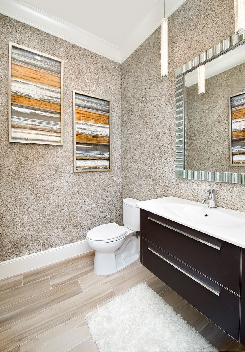 This bathroom offers a toilet and a floating sink vanity paired with a chrome framed mirror.