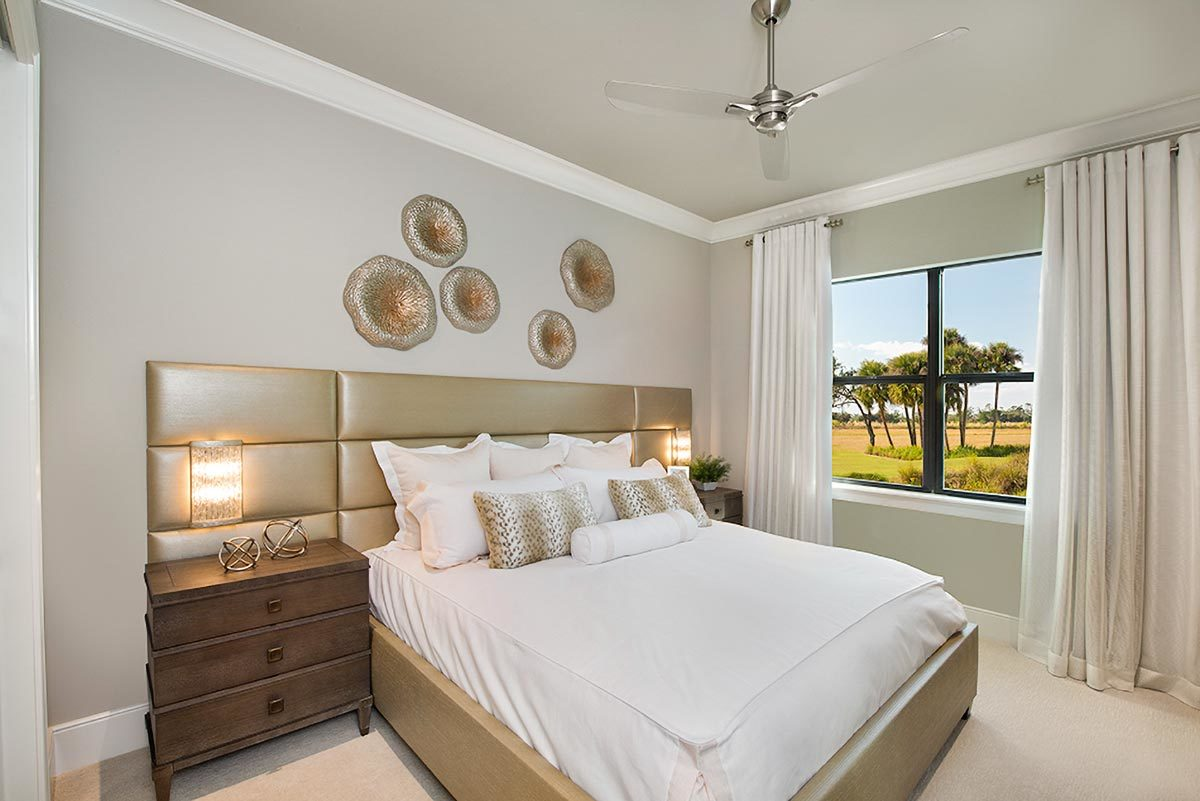 This bedroom features a chrome ceiling fan and a cozy bed with a huge custom headboard under the round brass decors.
