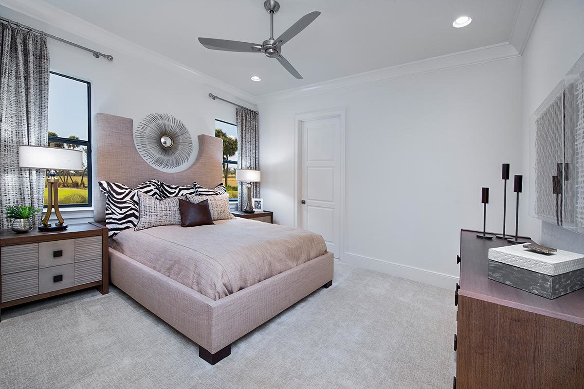 Another bedroom with a custom bed flanked by wooden nightstands and drum table lamps.
