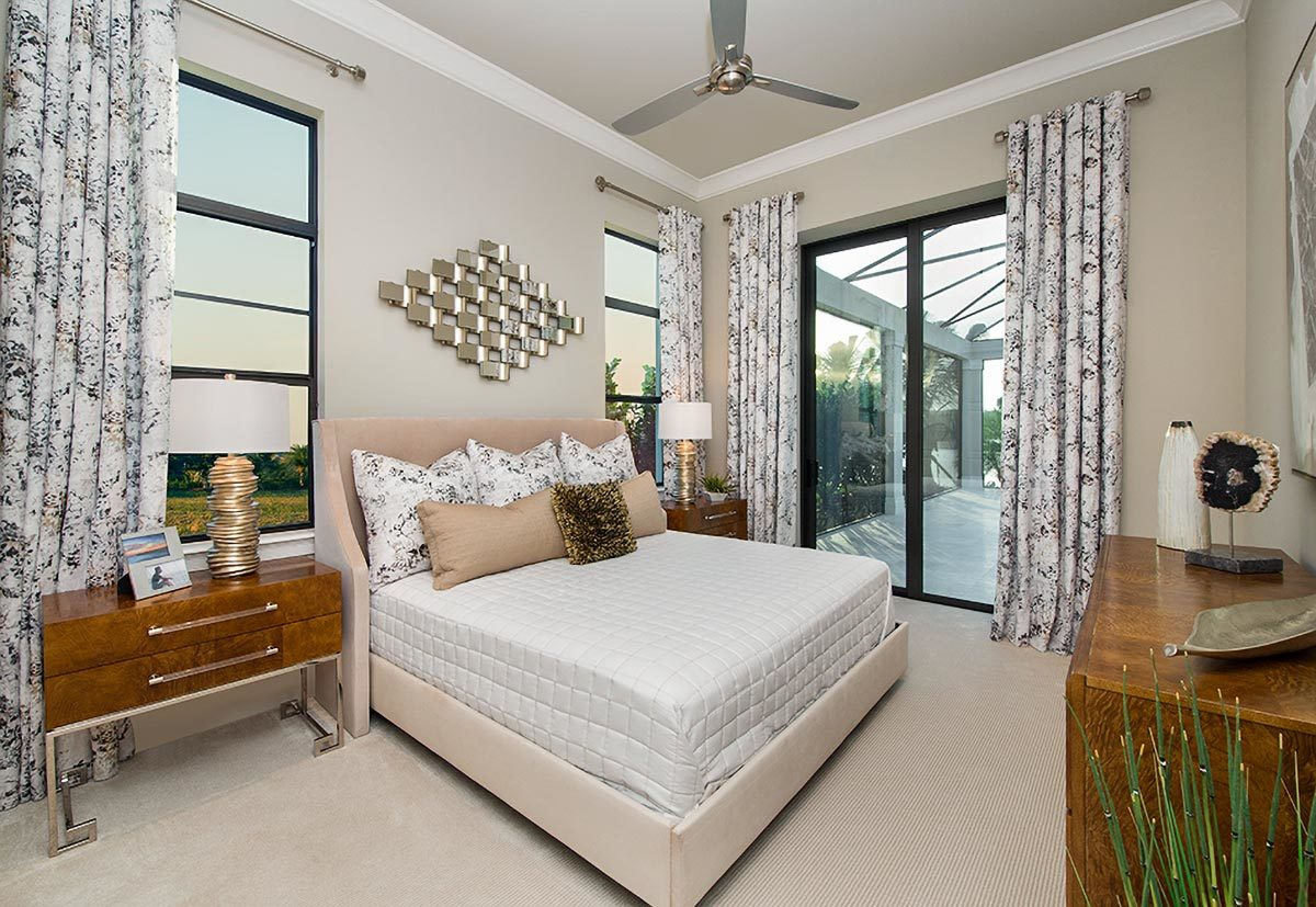 This bedroom has an earthy palette and glass sliders that lead out to the rear patio.
