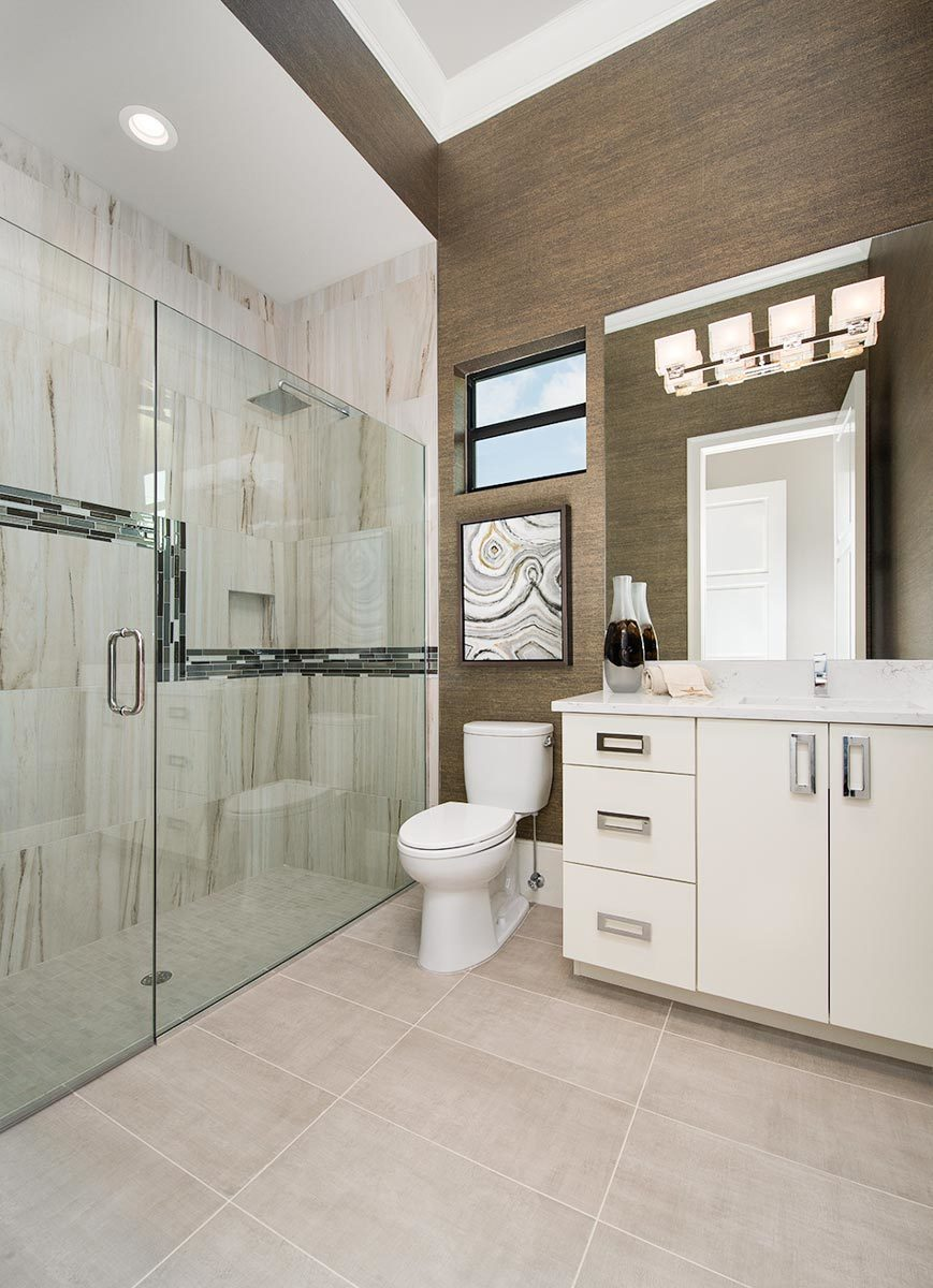 This bathroom offers a shower area, a toilet, and a sink vanity lit by glass sconces.