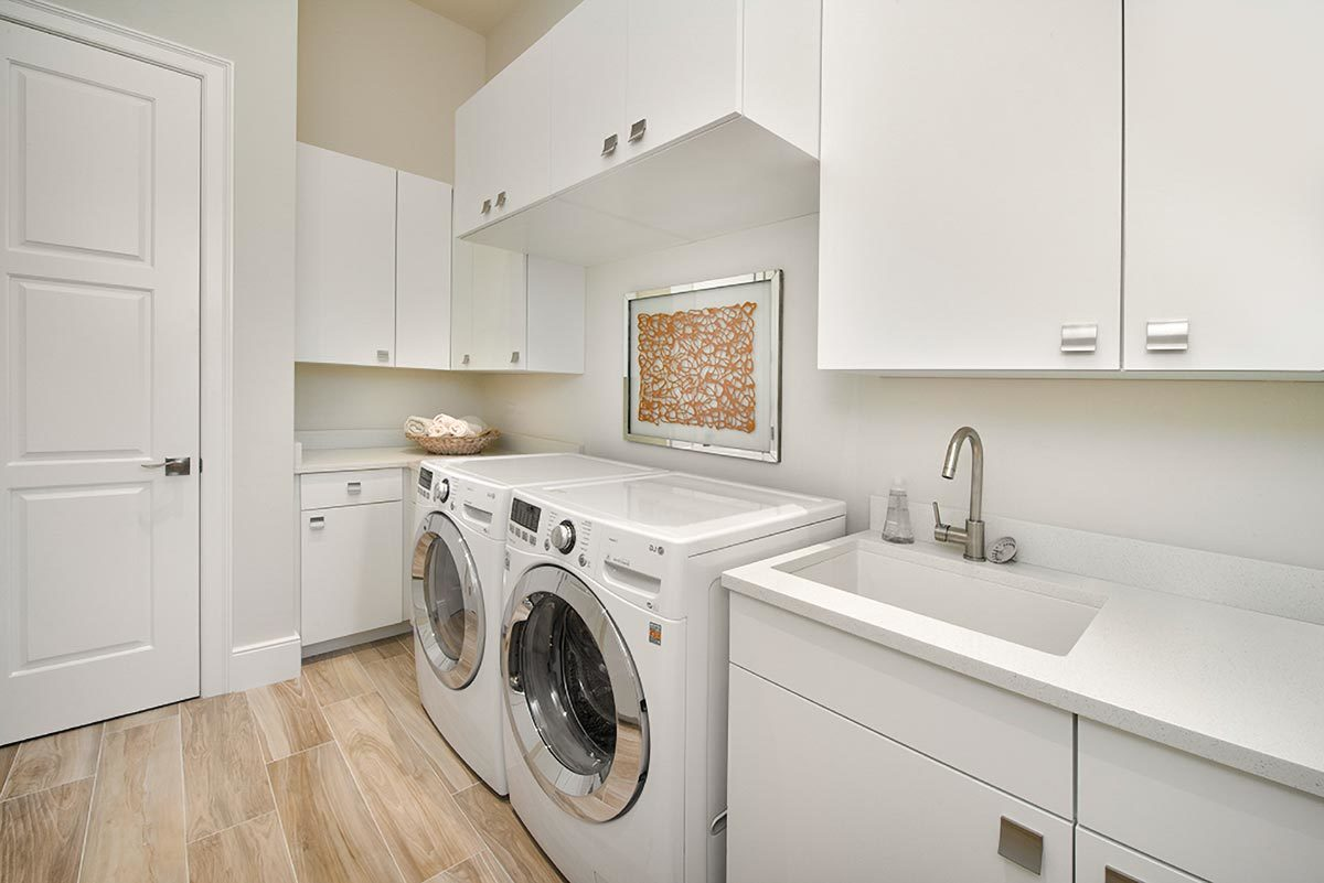 The laundry room is filled with white appliances and sleek cabinets that blend in with the pristine walls.