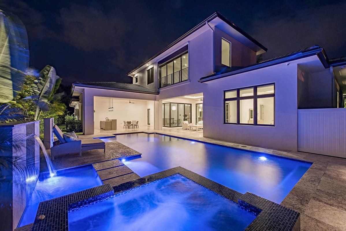 Night view of the home's rear showcasing the mesmerizing pool with a spa and water features.