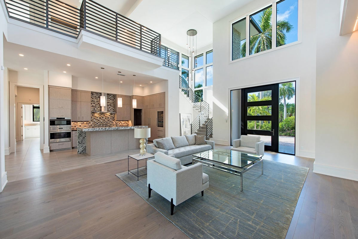 A farther view shows the kitchen behind that's flooded with ambient light from the recessed ceiling lights and glass pendants.