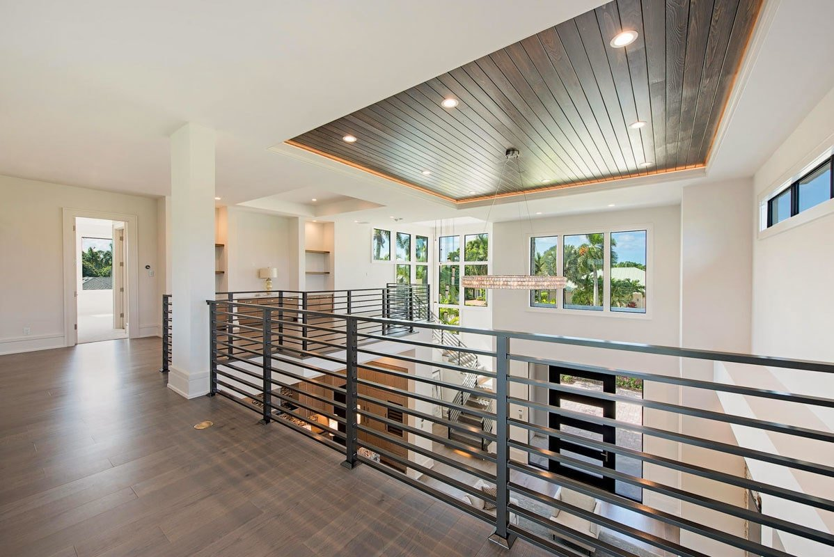 Second-floor balcony framed with white interior columns and modern wrought iron railings.