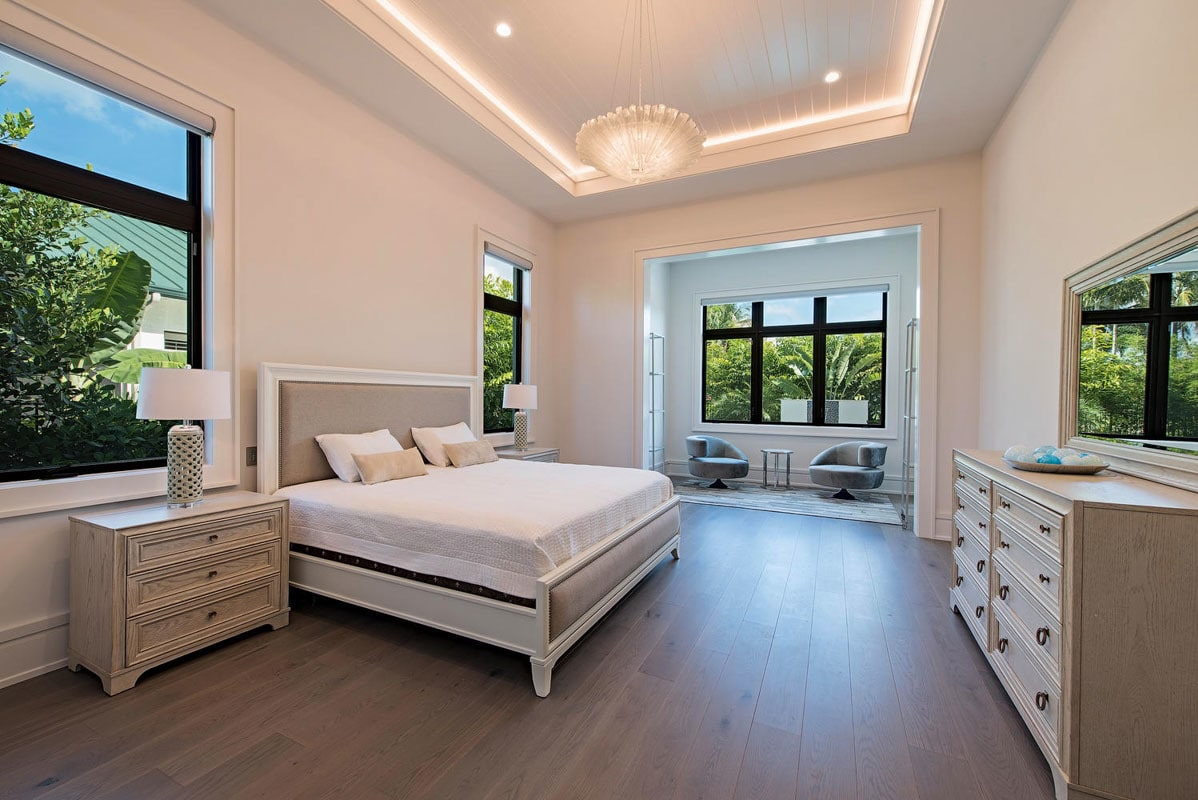The primary bedroom features a glowing tray ceiling and a sitting area filled with contemporary round armchairs.