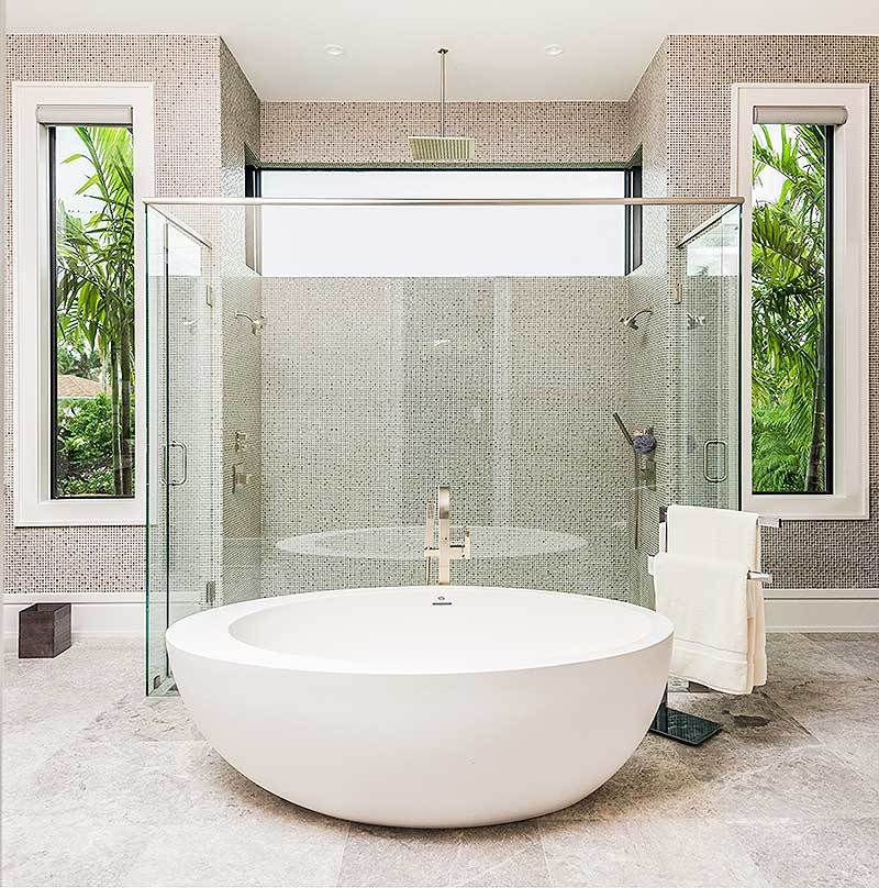A closer look at the deep soaking tub and large shower with chrome fixtures and glass enclosure.