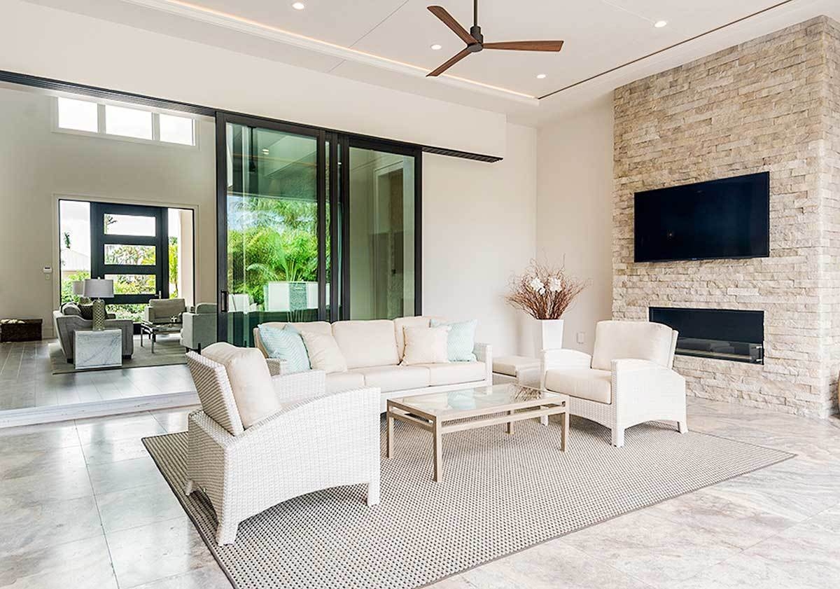 The covered lanai is filled with light wicker seats, a wall-mounted TV, and a modern fireplace fitted on the brick wall.