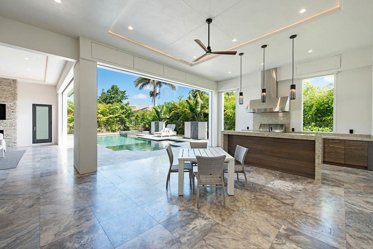 Outdoor kitchen with marble tiled flooring and a tray ceiling lined with ambient light.