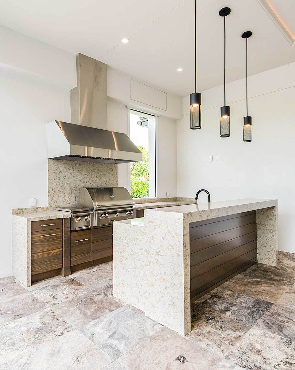 A closer look at the kitchen shows the dark wood cabinets, elegant granite countertops, and a two-tier island lit by black pendants.