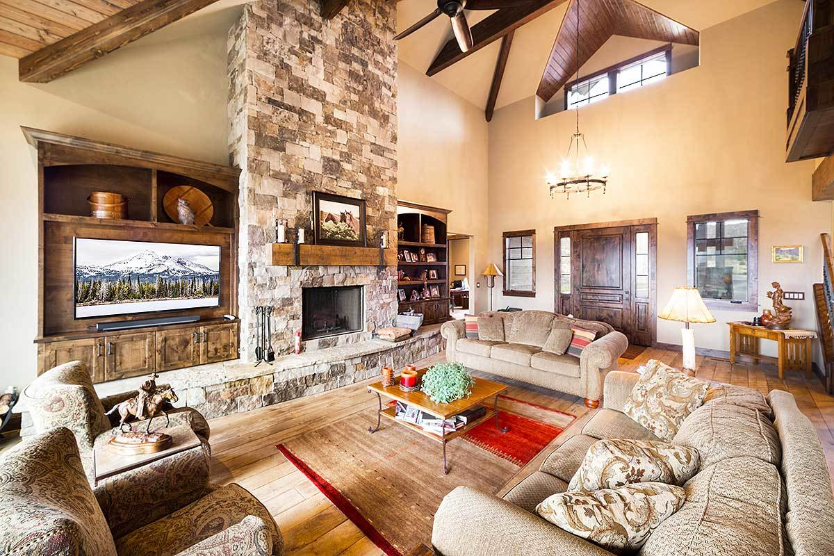 The living room has comfy beige seats and a stone fireplace flanked by the TV and the wooden bookcase.