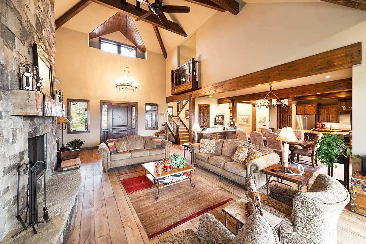 Behind the living room is the shared dining and kitchen defined with rustic wood trims.