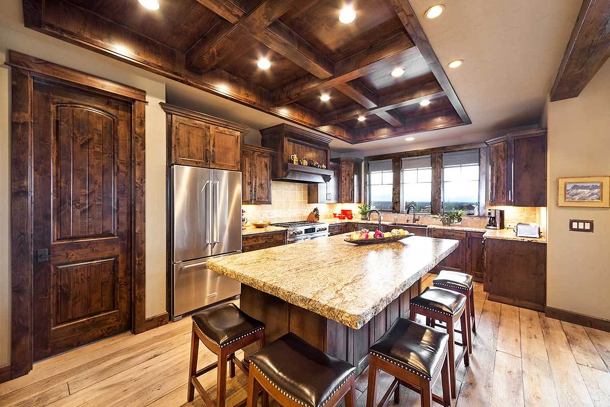 The kitchen is flooded with natural and ambient lights coming from the glazed windows and recessed lights fitted on the coffered ceiling.