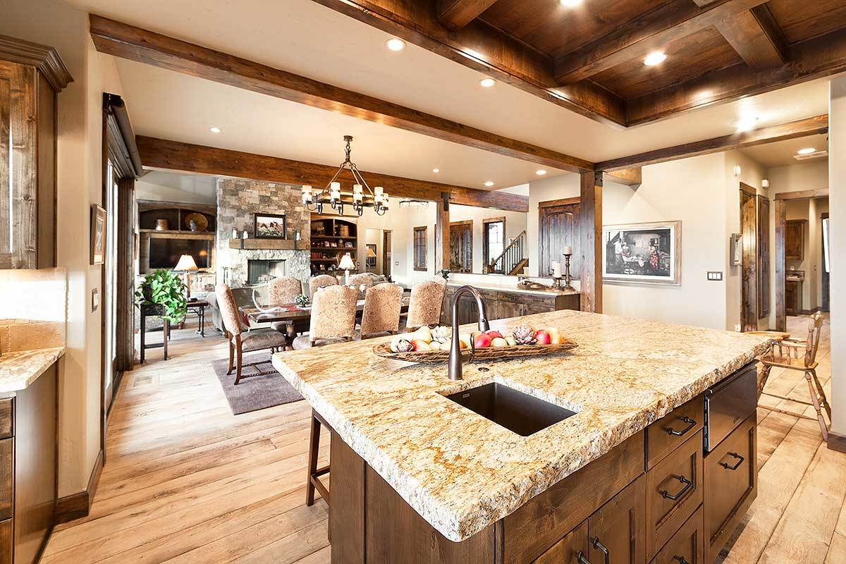 The kitchen island has dark wood pull-outs, a granite countertop, and an undermount sink paired with a gooseneck faucet.