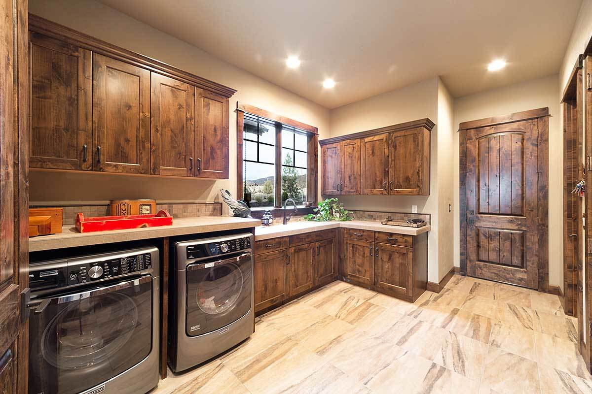 Laundry room equipped with stainless steel appliances and natural wood cabinets that match the rustic door.