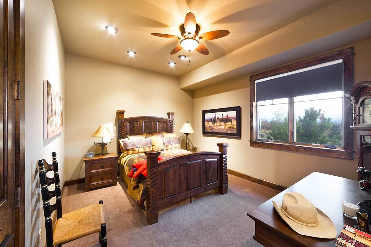 This bedroom has carpet flooring and beige walls adorned with various artworks.