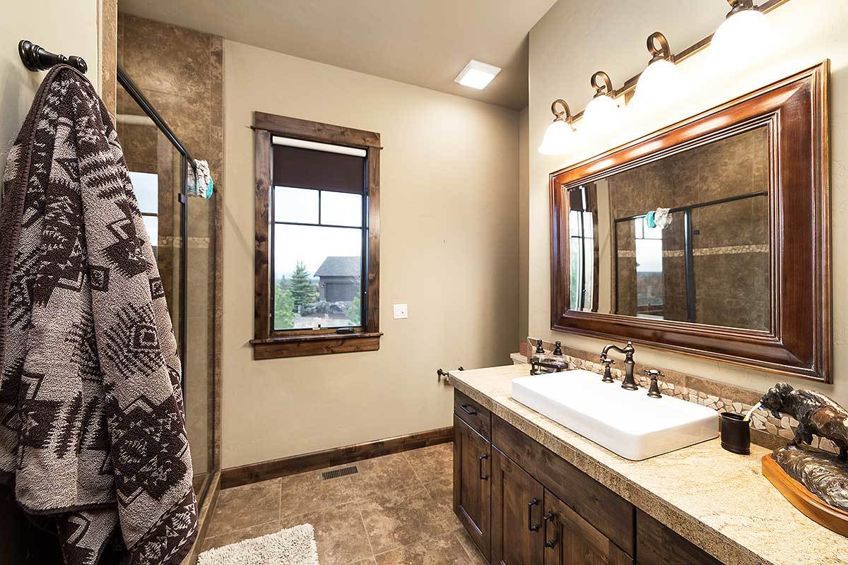The bathroom offers a walk-in shower and a wooden vanity with vessel sink and wrought iron fixtures.