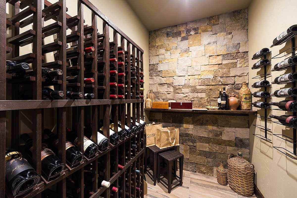 Wine cellar with column shelving, wall-mounted racks, and a floating shelf fixed against the brick accent wall.