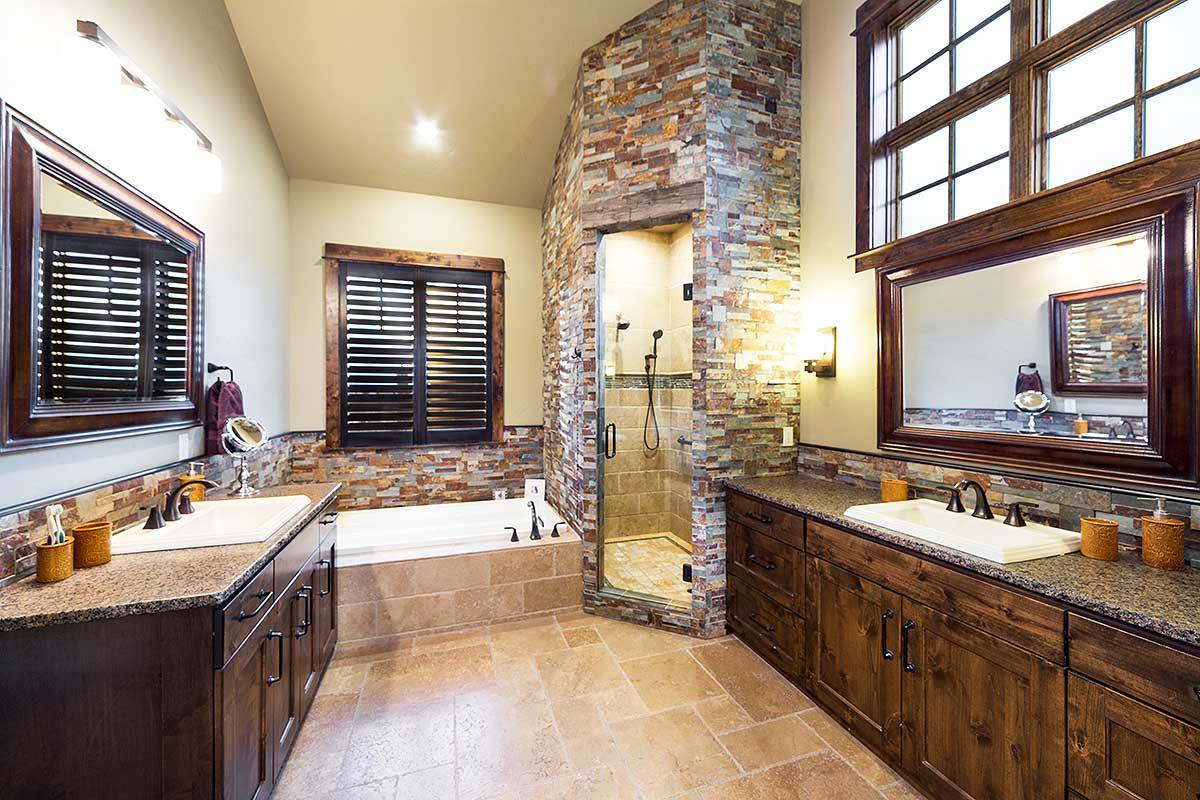 The primary bath is equipped with a deep soaking tub, a separate shower, and facing granite top vanities.
