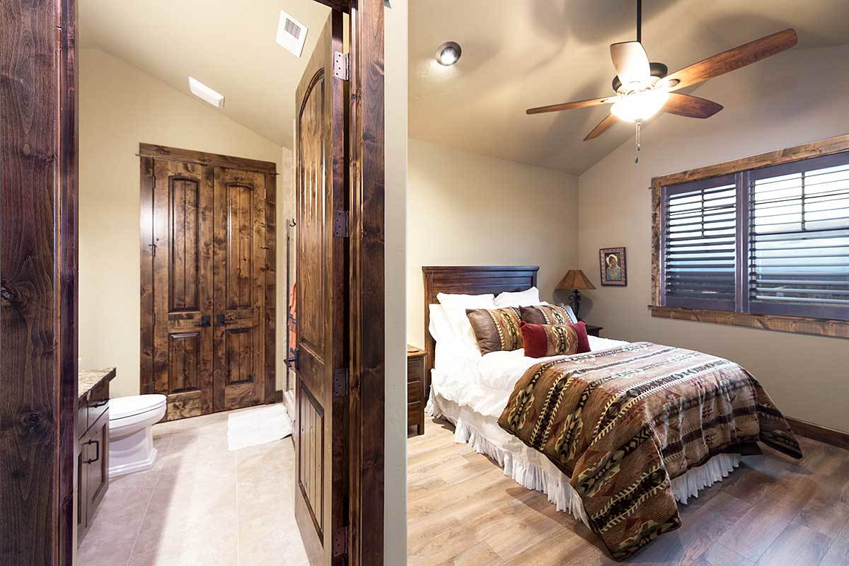 This bedroom has louvered windows and a dark wooden door that opens to the private bath.