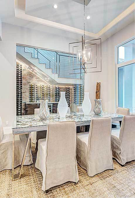The formal dining room offers a stylish modern chandelier, beige skirted seats, and a glass dining table topped with gorgeous vases.