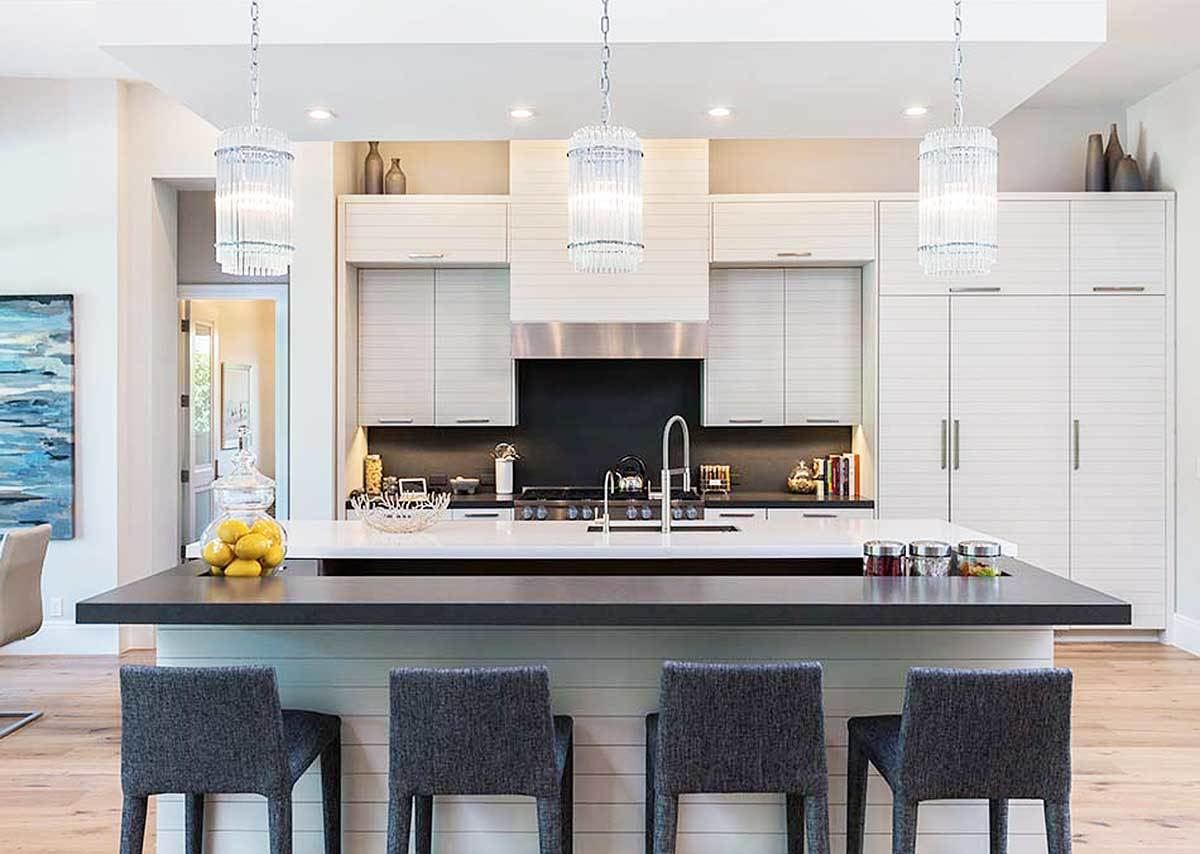 A closeup look at the two-tier island limed with glass pendant lights and gray counter chairs.