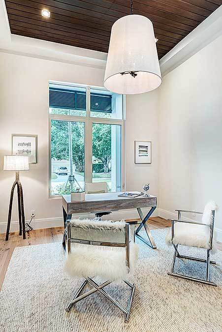 The study offers a large pendant lamp, sleek desk, and furry chairs sitting on a textured area rug.