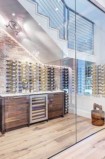 Wine storage situated underneath the staircase boasting column shelves and a bar fitted with a wine fridge.