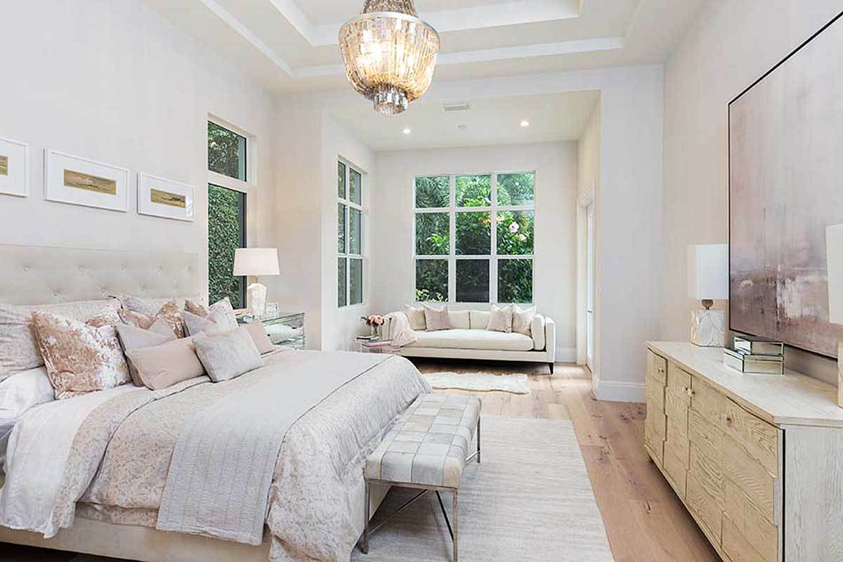 The master bedroom has a gorgeous step ceiling and a sitting area by the white framed window.