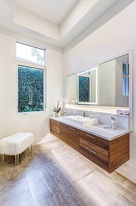 Master bathroom with a floating vessel sink vanity complemented with a rectangular mirror and a white faux fur stool.