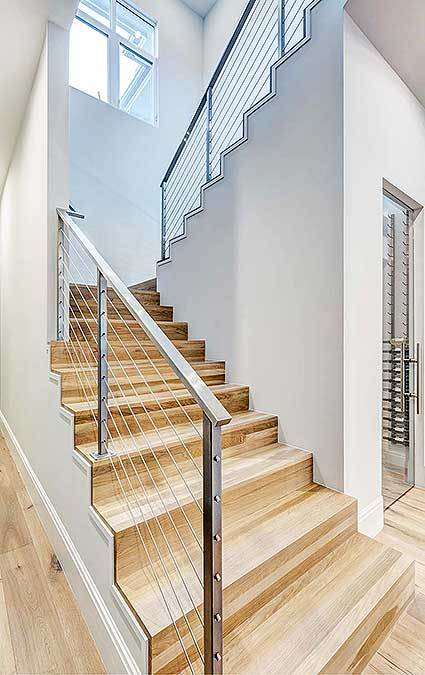 A sleek staircase with metal railings and wooden steps blending in with the hardwood flooring.