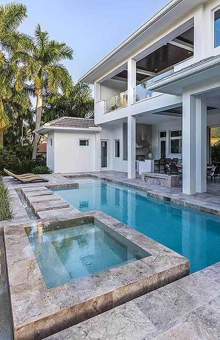 The swimming pool with an integrated spa has limestone paving and a fire pit.