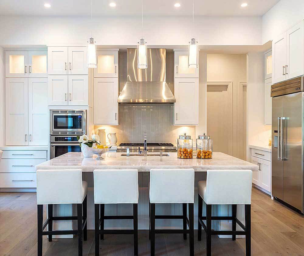 The kitchen is equipped with stainless steel appliances, white cabinetry, and an undermount sink fitted on the marble top island.