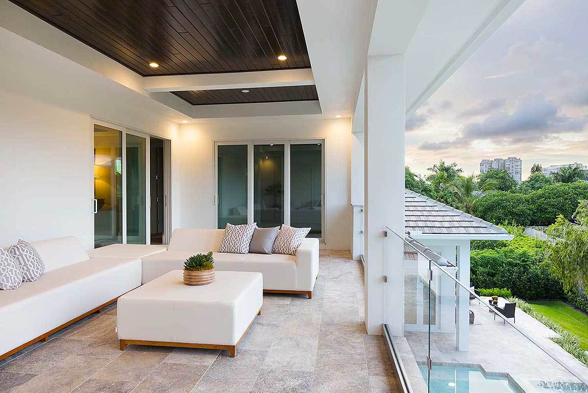 Covered balcony with sleek white sofas and a matching ottoman over limestone flooring.