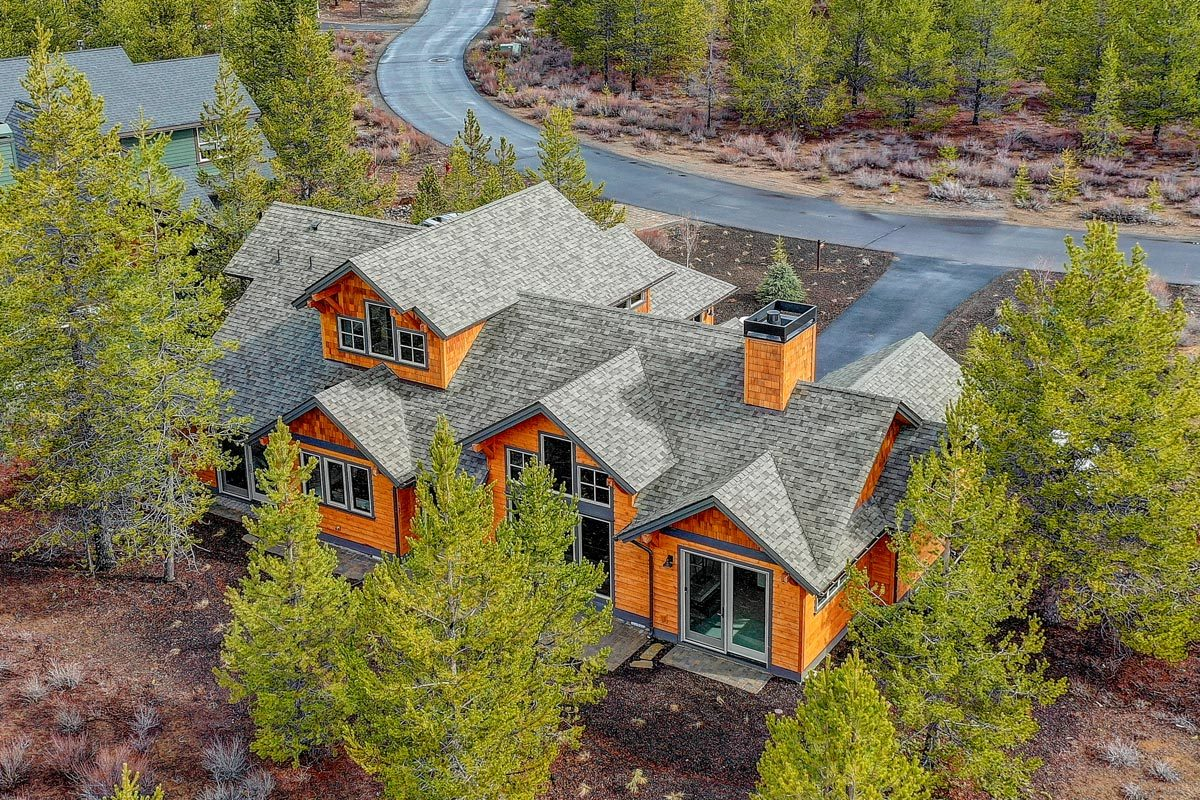 The home is complemented with a curved driveway and towering pine trees that add privacy.