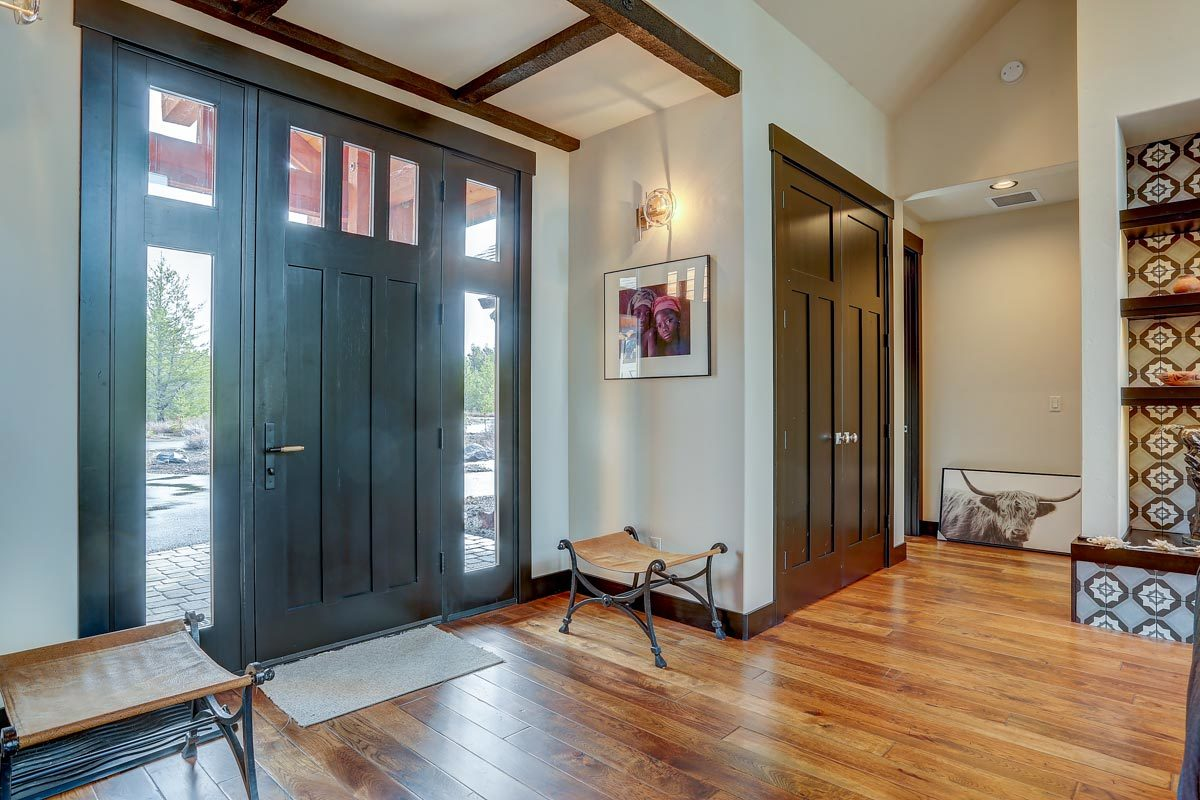 The foyer has a dark wood front door and a small rug flanked by metal stools.