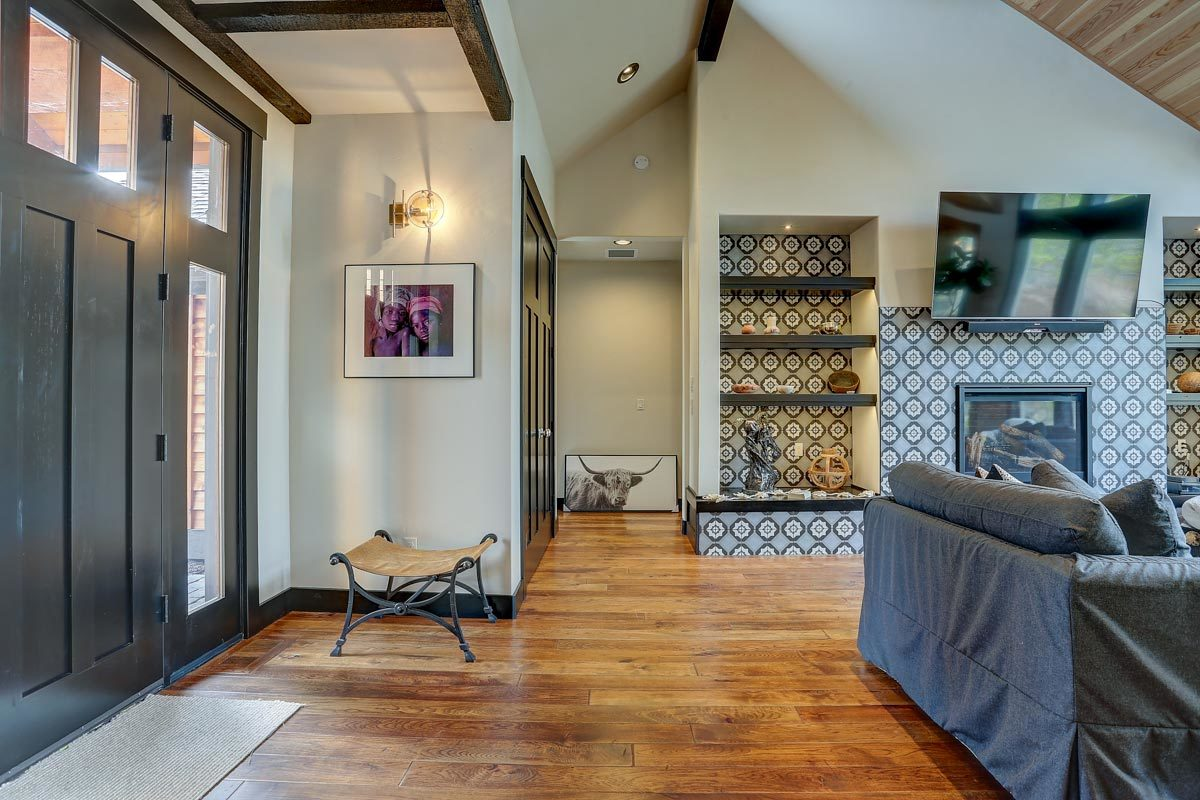 A hallway nestled in between the foyer and living room that leads to the two bedrooms.