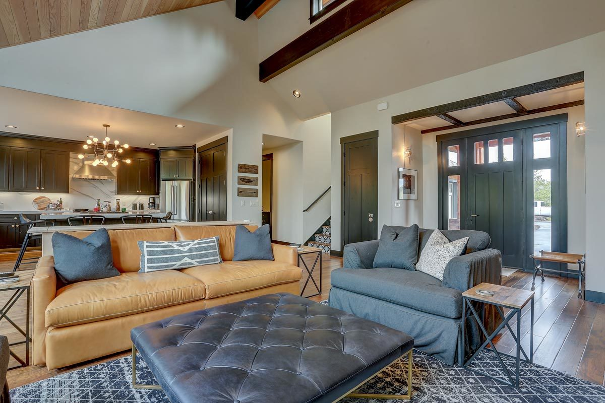 The living room offers cozy sets, metal side tables, and a tufted ottoman sitting on a patterned area rug.