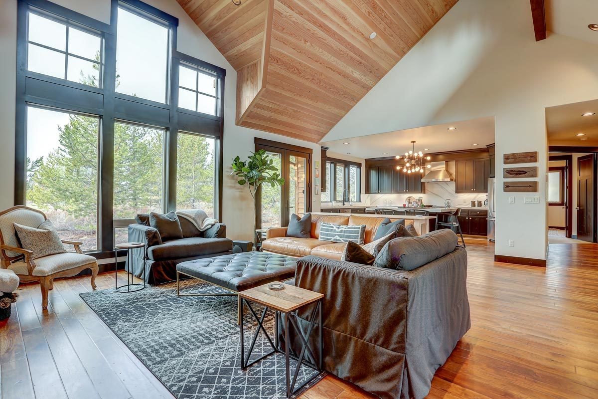The open living room has a soaring vaulted ceiling and natural hardwood flooring topped with a patterned rug.