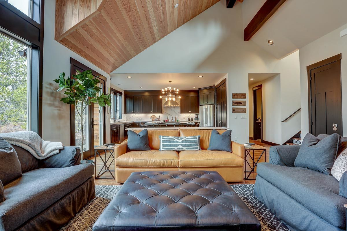 A closer view showcasing the tufted ottoman surrounded with gray and brown leather sofas.