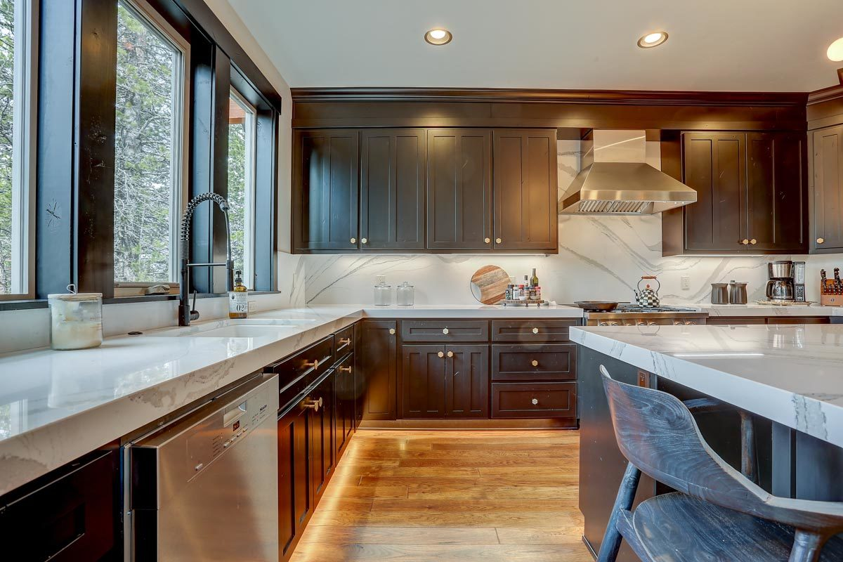 The kitchen offers an undermount sink paired with a wrought iron pull down sprayer.