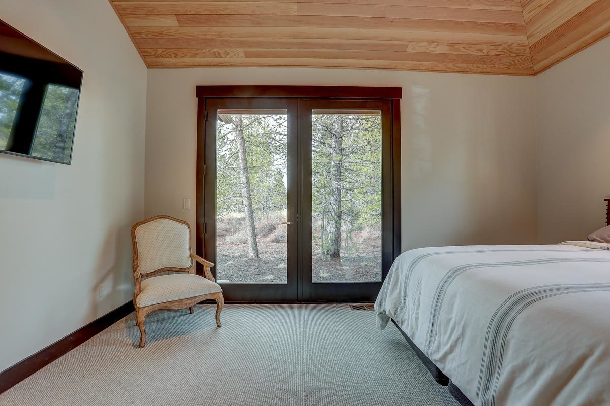 Glass double door of the primary bedroom complemented with a wooden cushioned chair.