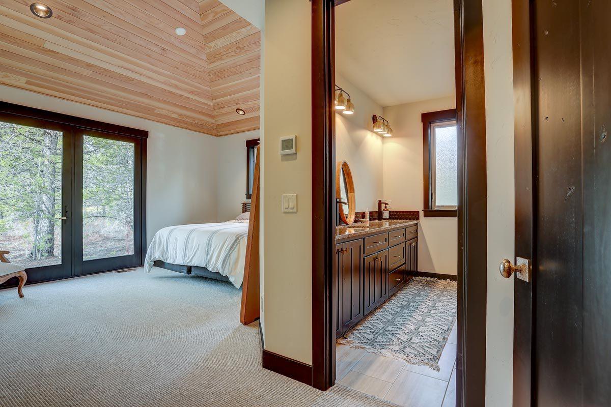 A glimpse at the primary bedroom's bath enclosed a dark wood door.