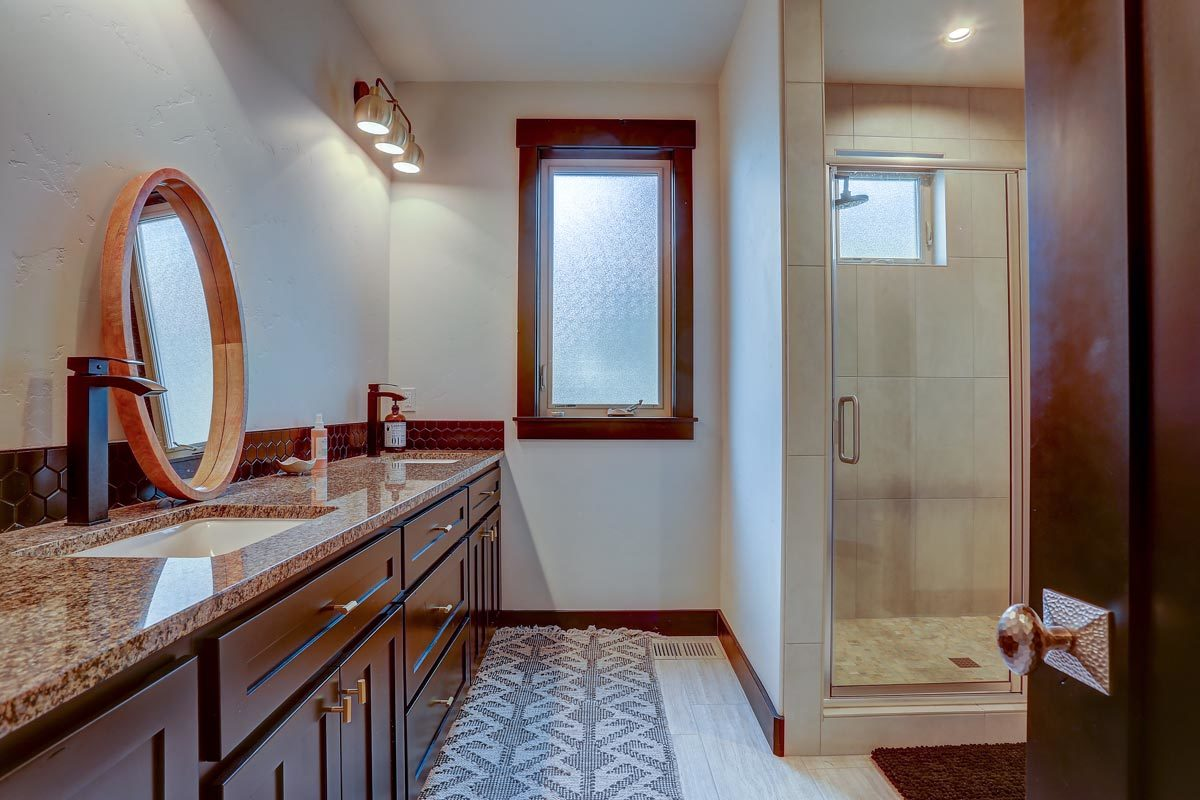 A closer look shows the walk-in shower and a large dual sink vanity topped with a round mirror.