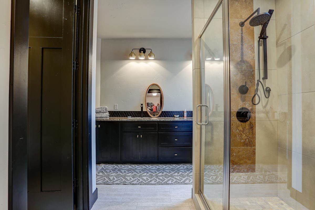 Another bathroom with a walk-shower and a dark wood vanity lit by warm sconces.
