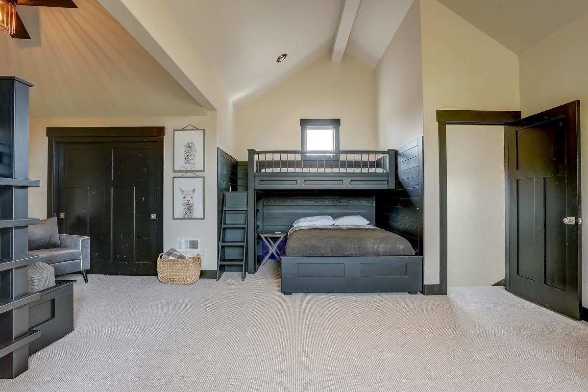 This spacious room is filled with bespoke bunk beds and a comfy gray armchair.