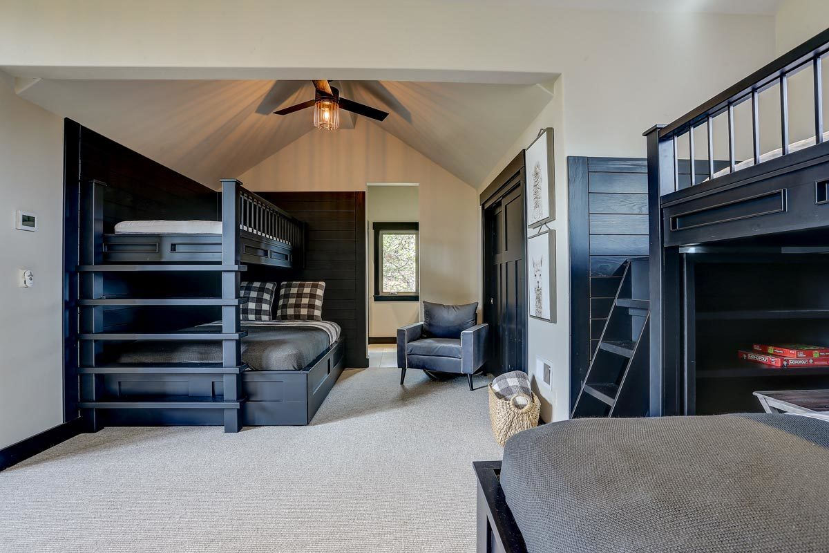 The room has beige carpet flooring and a vaulted ceiling mounted with a warm fan.
