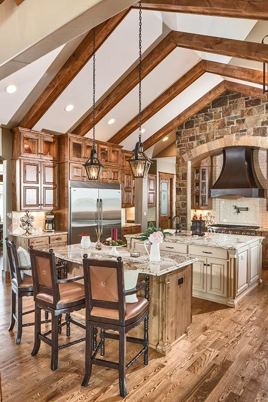 Heavy wood elements run throughout the kitchen. It is illuminated by lantern pendants and recessed lights fitted on the beamed cathedral ceiling.
